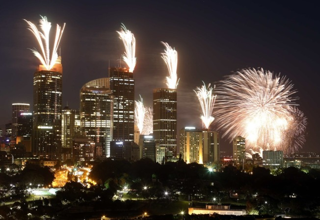 Image: Fireworks explode on the rooftops of buildings during a show prior to the new year celebrations in Sydney